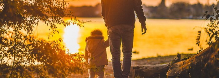 father and son holding hands while walking